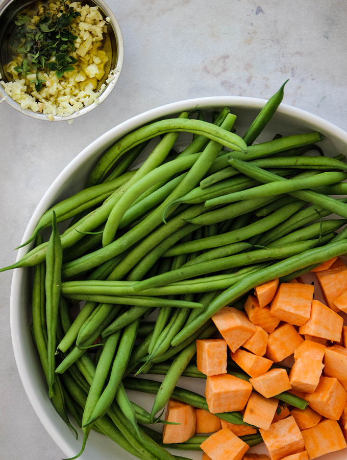 Oven Roasted Vegetables with Thyme is plated in a white bowl with a side dish of olive oil and garlic.