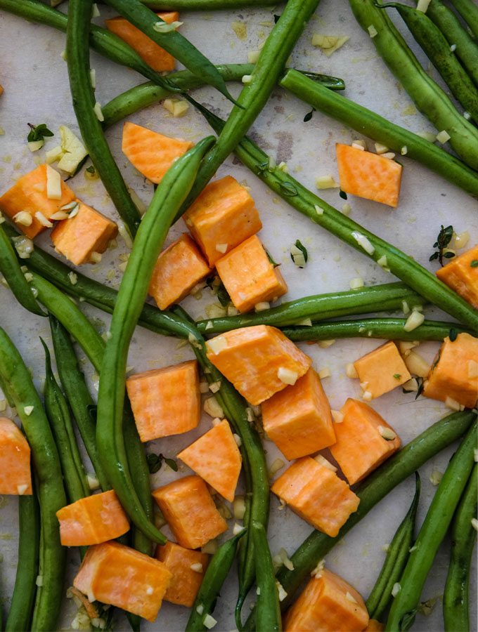 Sweet potatoes and green beans are tossed in olive oil, garlic, and fresh thyme.
