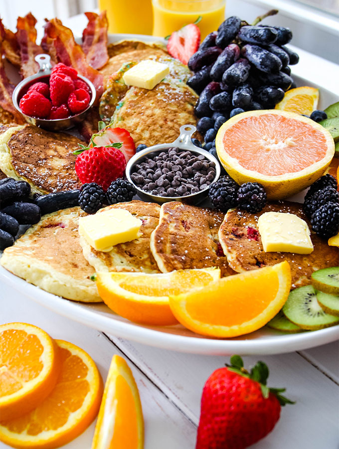 Pancake breakfast board is topped with powdered sugar and more fresh fruit.