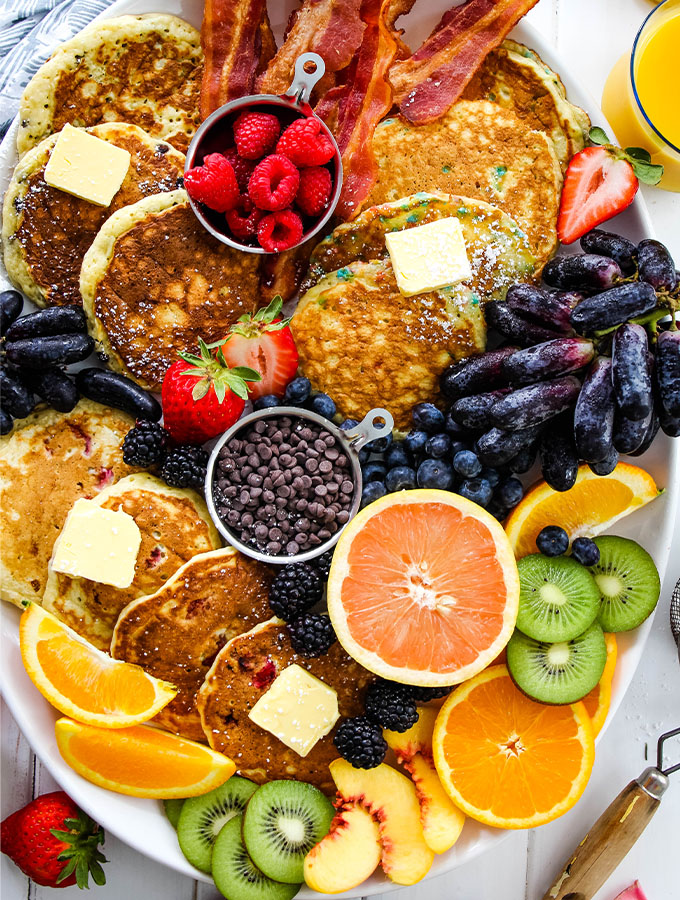 Pancakes and fresh fruit are displayed across a white serving tray.
