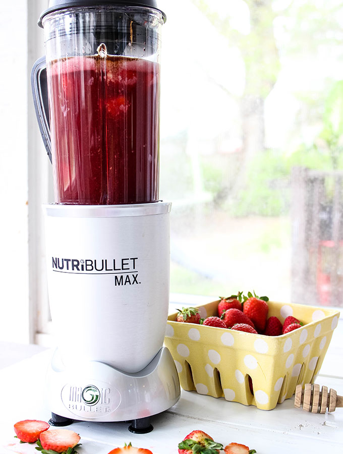 Pink drink is made in the blender with extra strawberries surrounding it.