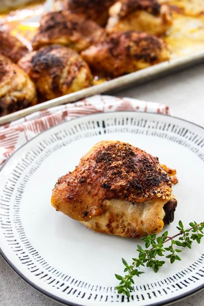 A chicken thigh is placed on a white plate with a sprig of thyme.