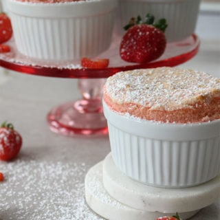 Strawberry Soufflé is baked in ramekins and dusted with powdered sugar.