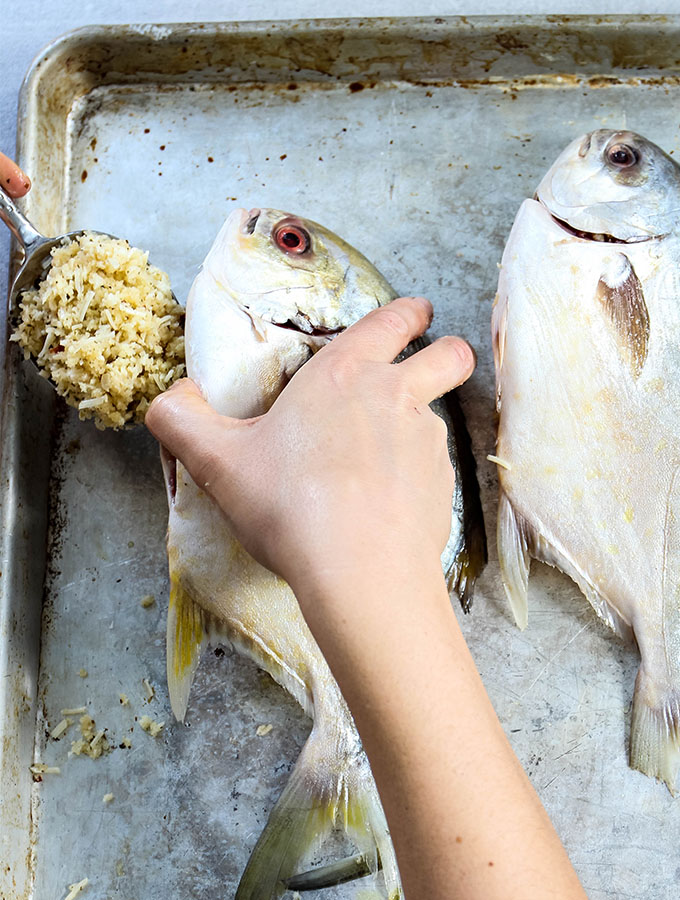 Two pompano fish are stuffed with white wine breading.