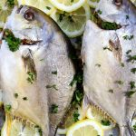 Pompano fish is plated over fresh sliced lemons and parsely.
