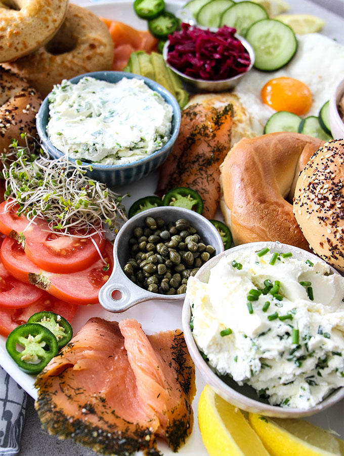 Lox and bagels breakfast board is displayed with all the fixings and cream cheese.