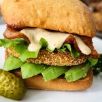 Fried green tomato BLT sandwich is plated with a pickle.