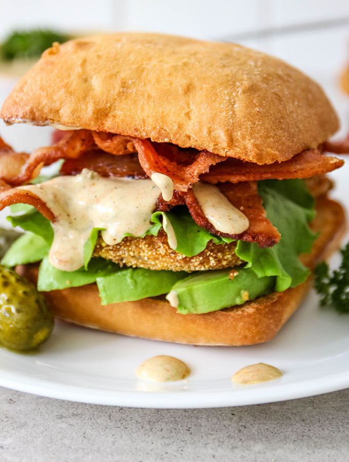 Cajun remoulade sauce is dripping down a fried green tomato BLT sandwich.