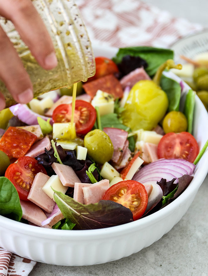 Salad dressing is drizzled of the Italian salad and plated in a bowl.