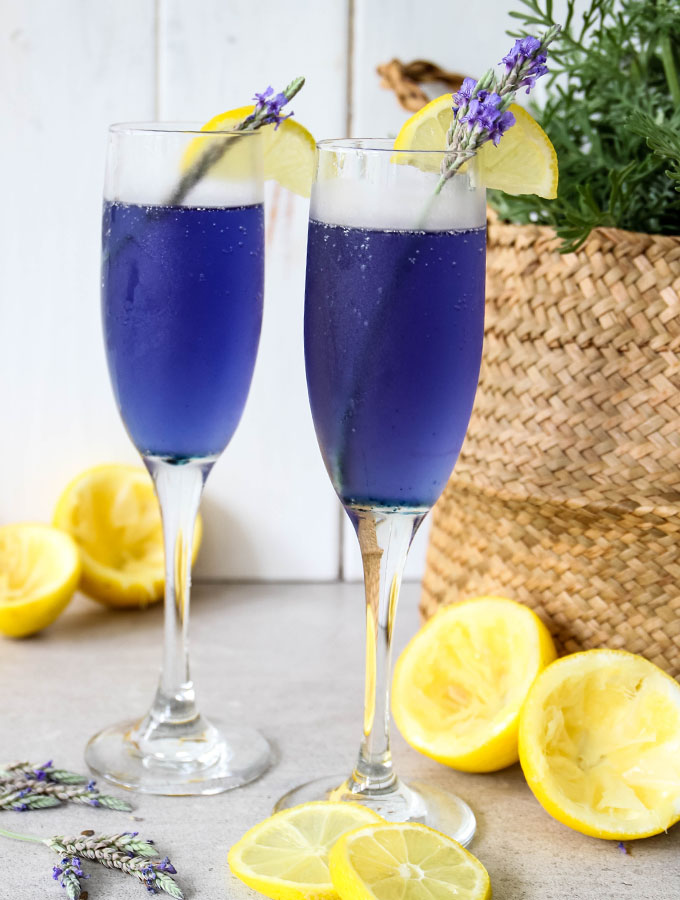 Lavender Lemonade Mimosas are poured in small flutes and topped with lemon wedges.