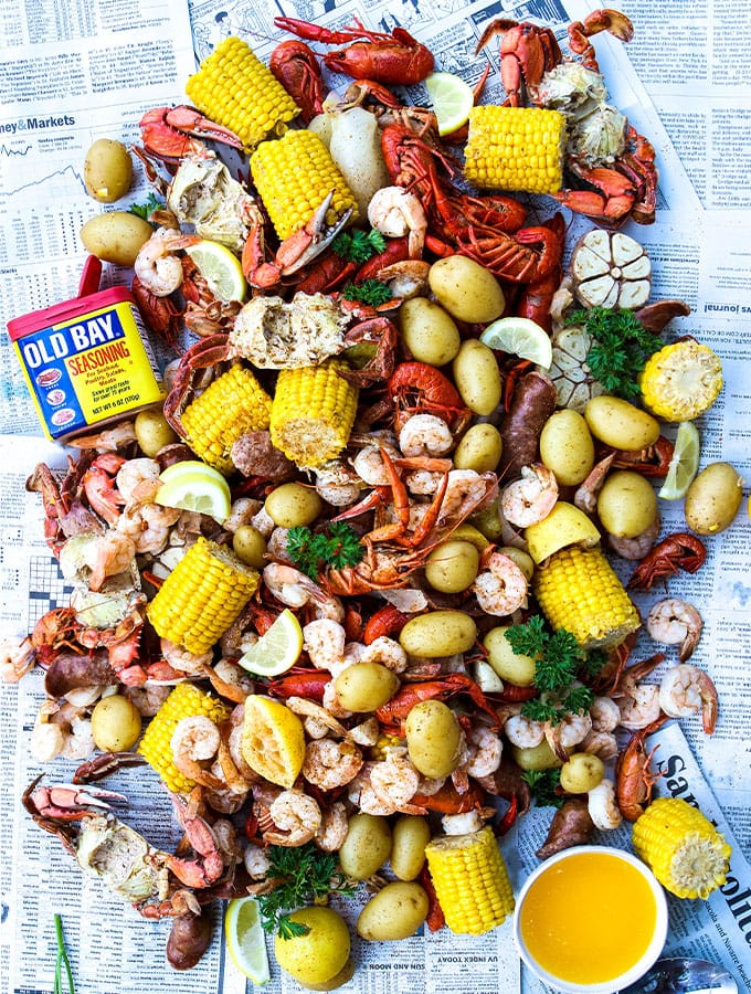 A low country boil is tossed on a newspaper and served with melted butter.