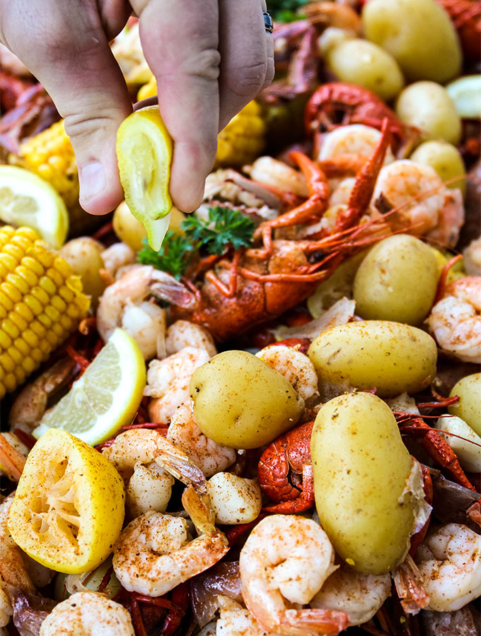 A wedge of lemon is squeezed over the low country boil.
