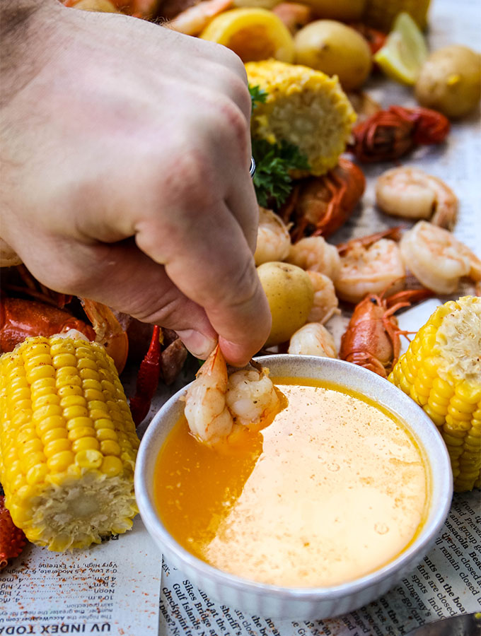 A hand is dipping a shrimp in cajun lemon butter.