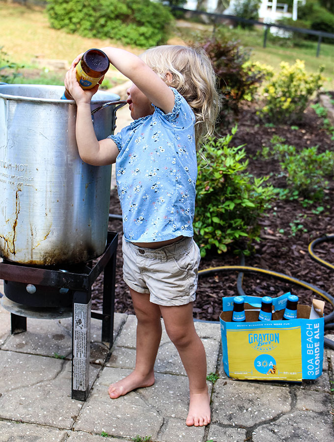 Evelyn is pouring a glass of beer into a stockpot.