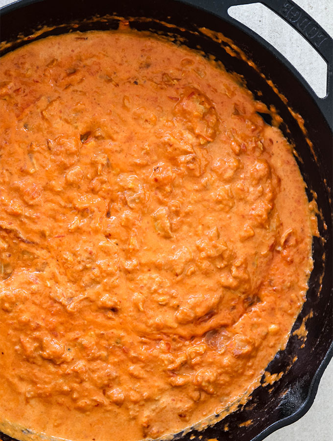 Penne alla vodka sauce is simmered in a large cast iron pan.