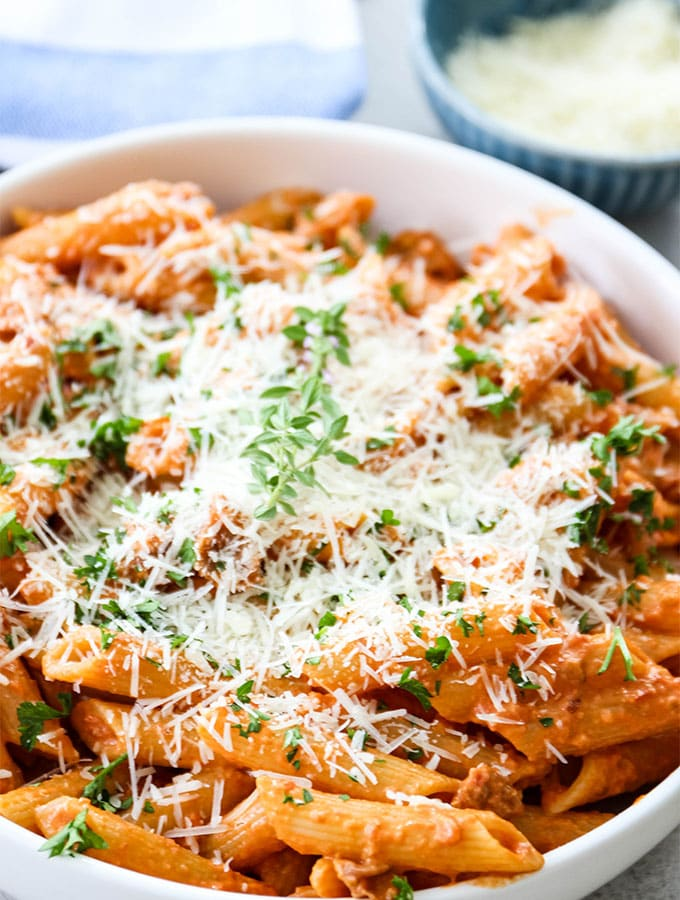 Penne alla vodka is plated and topped with parmesan cheese and parsley.