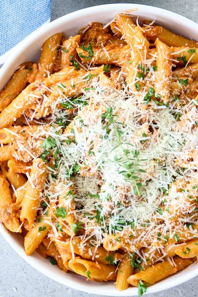 Penne alla vodka is topped with freshly grated parmesan cheese.