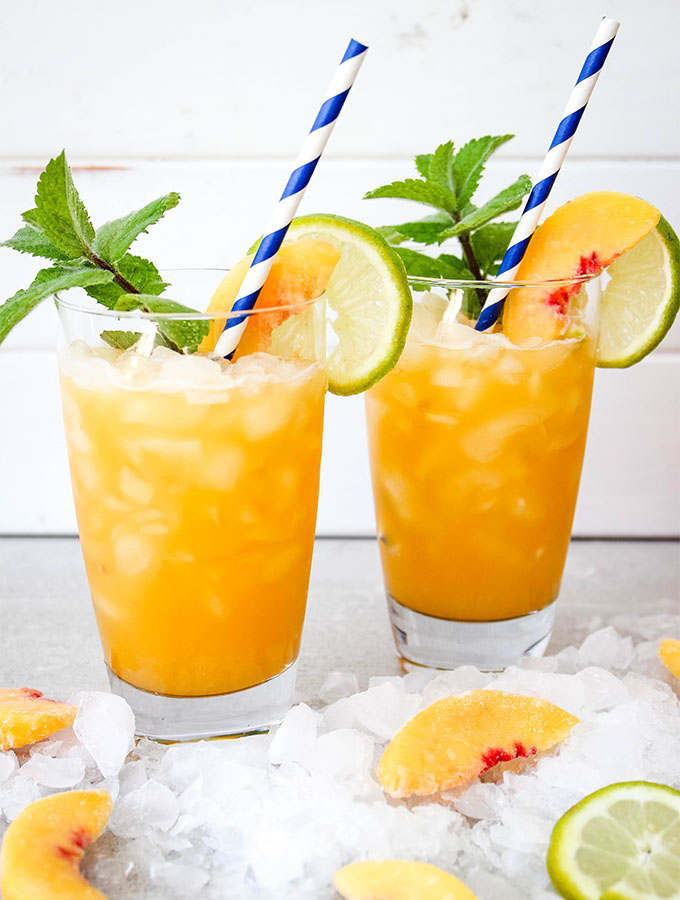 Agua fresca is poured over ice and topped with more fresh fruit and a straw.