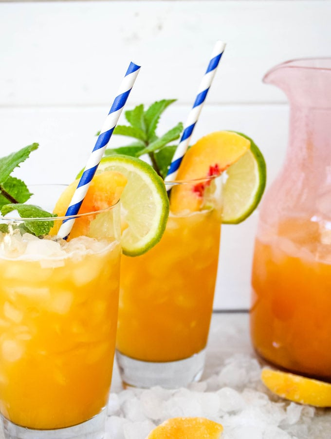 Agua fresca is poured from a pitcher into two cups of ice.