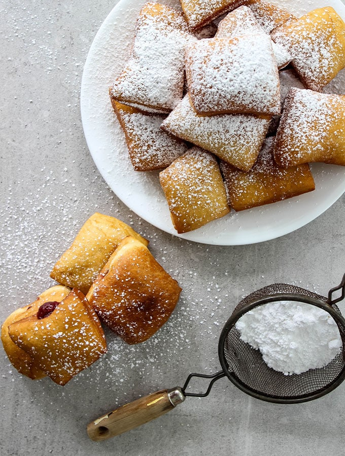 Beignets are plated and dusted with powdered sugar.