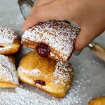 A hand is picking up a raspberry filled beignet.