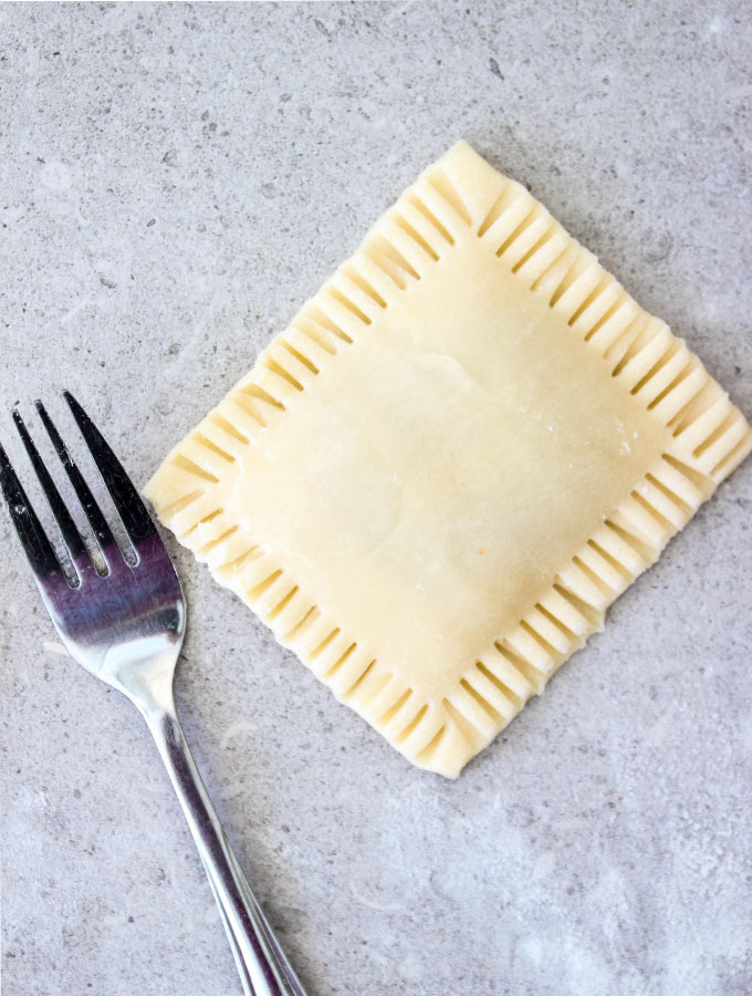 A fork is used to press and seal the edges of the pop tart.