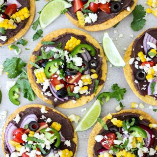 Vegetarian tostadas are topped with all the fixings and wedges of lime.