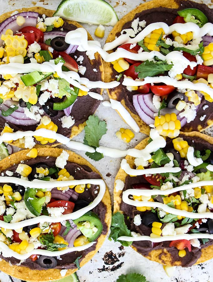 Vegetarian tostadas are topped with all the fixings and sour cream.