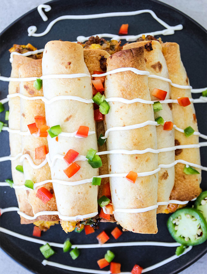 Breakfast taquitos are baked, then staked and topped with sour cream.