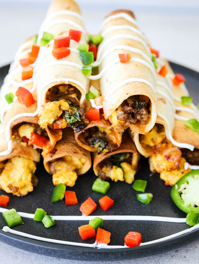 Breakfast taquitos are stacked and plated with jalapeno slices.