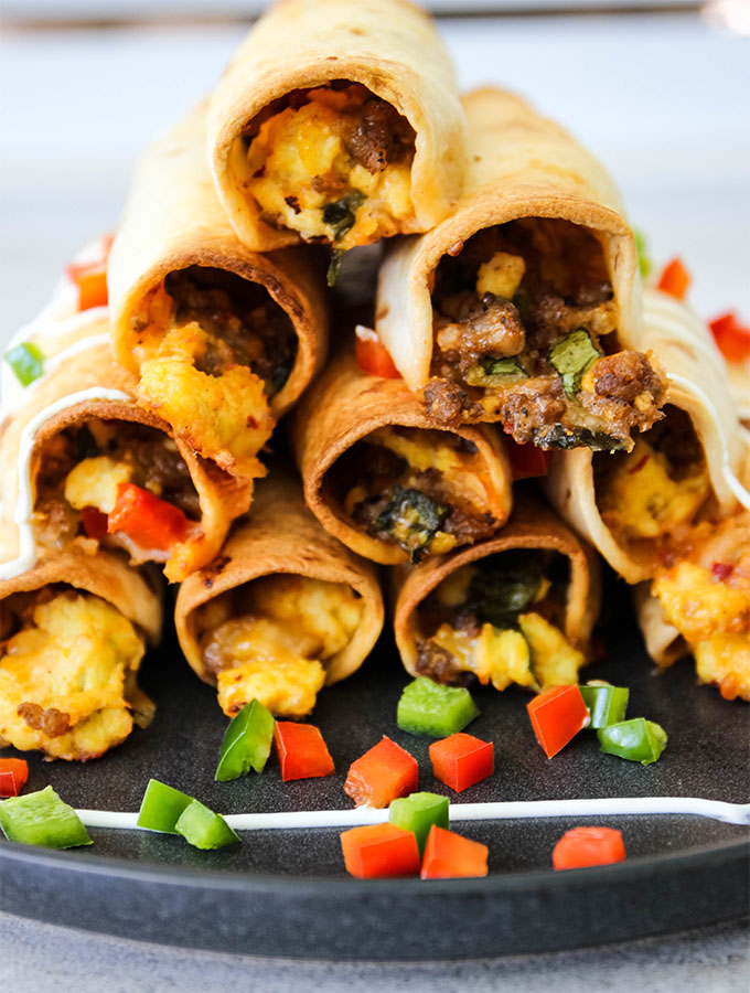 Baked breakfast taquitos are stacked and topped with diced bell peppers.