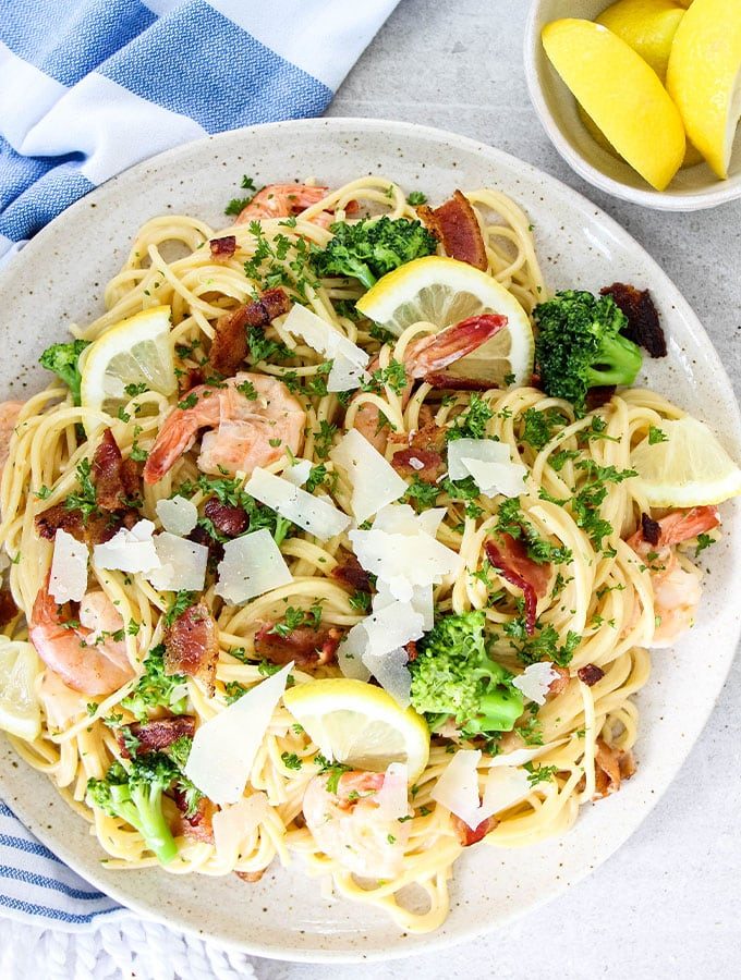 Creamy Bacon and Shrimp Scampi is plated and topped with parmesan cheese and lemons.