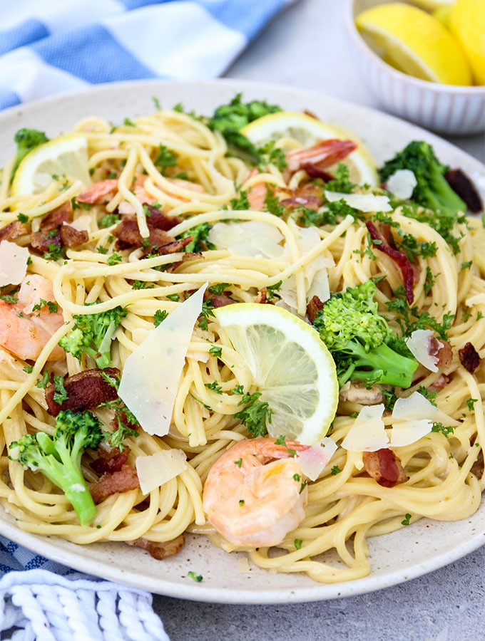 Creamy Bacon and Shrimp Scampi is plated on a white plate and topped with shaved parmesan cheese.