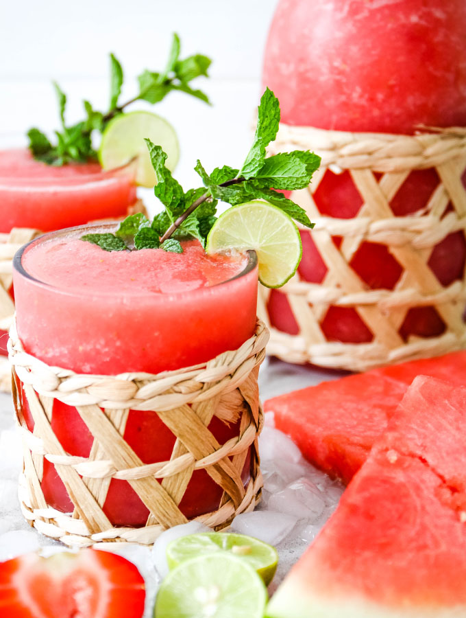 Frozen Strawberry Watermelon Margaritas is poured into small individual glasses and topped with fresh mint and limes.