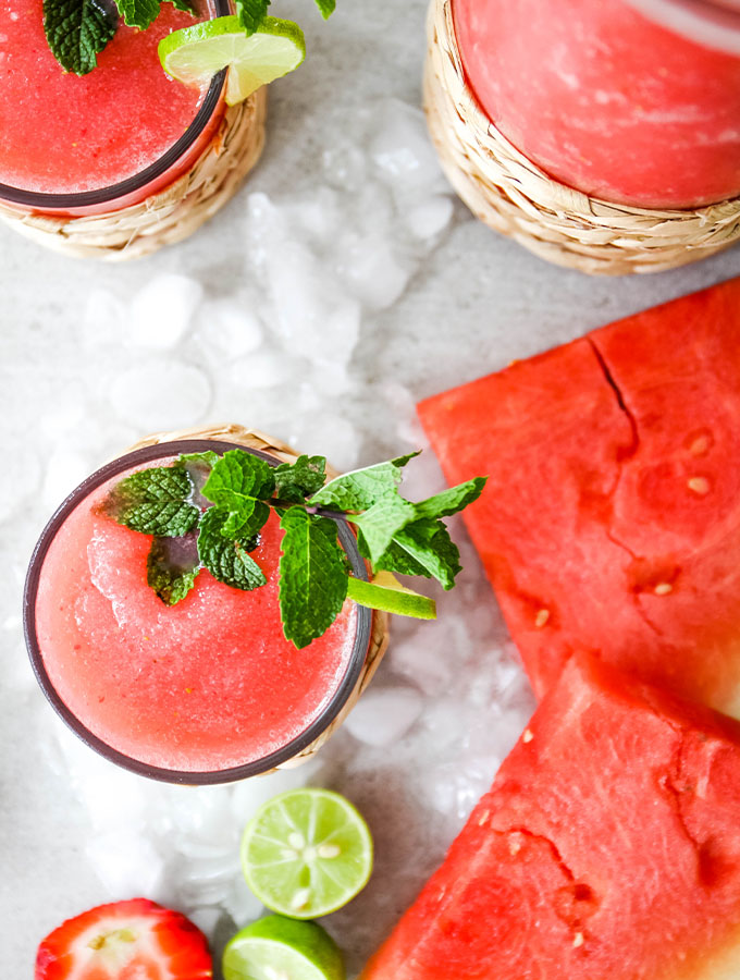 Frozen Strawberry Watermelon Margaritas are poured into individual glasses and topped with fresh limes and mint.