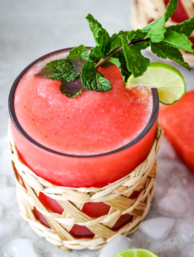 Frozen Strawberry Watermelon Margaritas is poured into a small glass and topped with fresh mint.