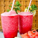Frozen hibiscus lemonade is poured into separate glasses and topped with mint sprigs and straws.