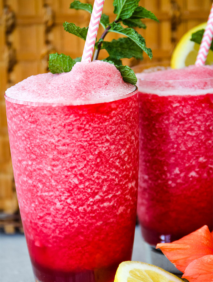 Frozen hibiscus lemonade is poured into separate glasses and topped with straws.