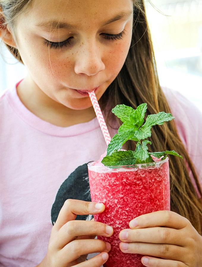 Ava is drinking frozen hibiscus lemonade through a paper straw.