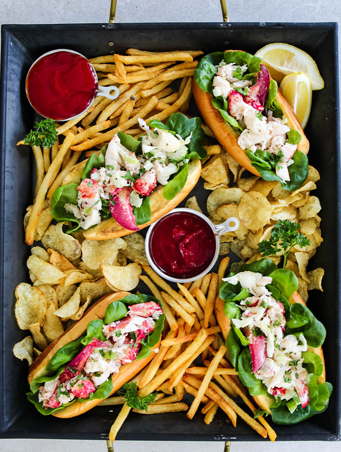 Lobster rolls are plated on a large serving platter with fries and chips.