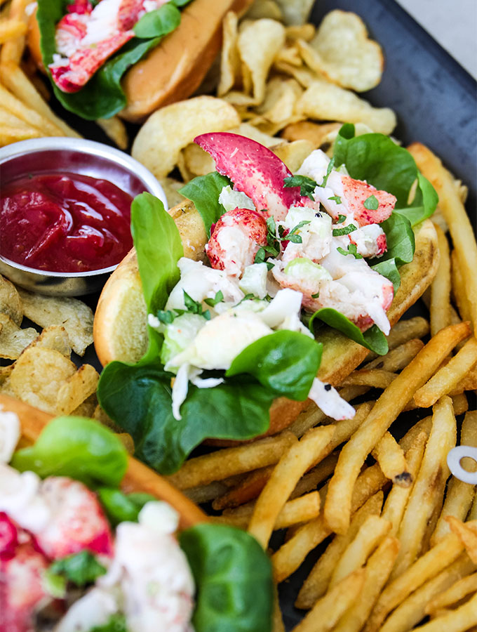 Lobster rolls are plated and served with fries, chips, and ketchup.