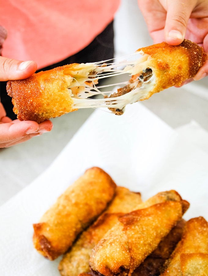 A Philly Cheese Steak Egg Roll is pulled apart, exposing stringy cheese.