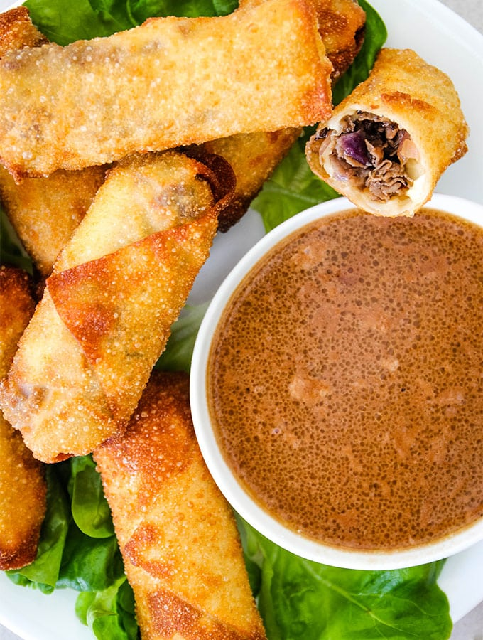 Philly Cheese Steak Egg Rolls are plated around a bowl of au jus sauce.