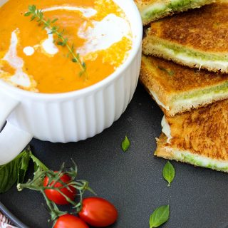 Tomato bisque and grilled cheese sandwiches are plated on a black plate and topped with fresh basil.