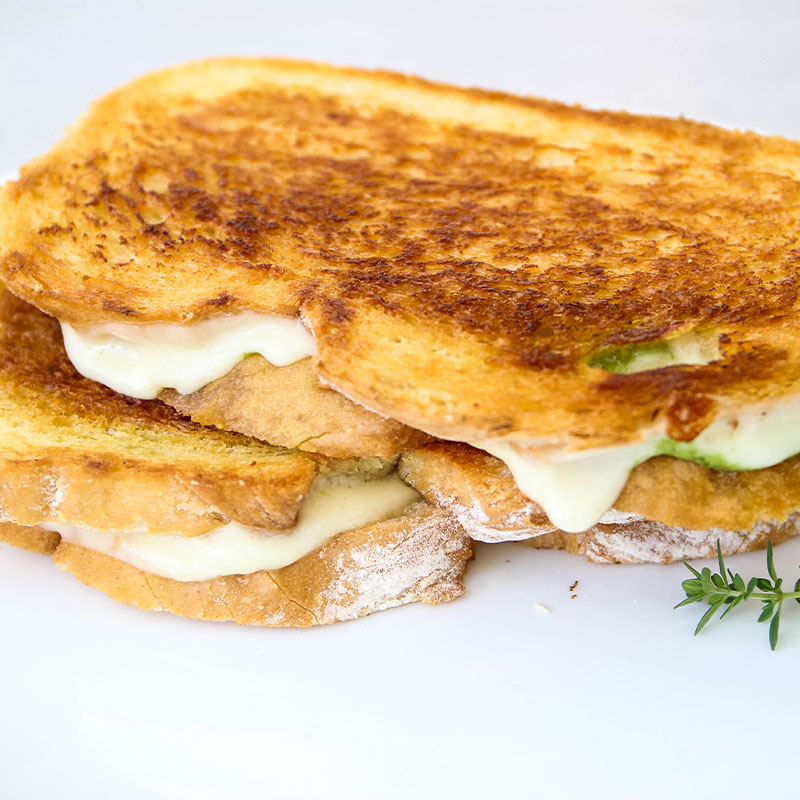 Pesto provolone grilled cheese sandwiches are plated on a white plate.