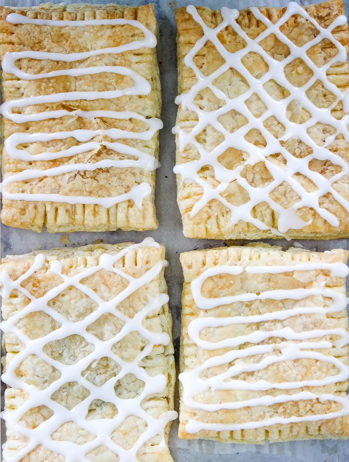 Homemade toaster strudels are topped with icing in a lattice deisng.