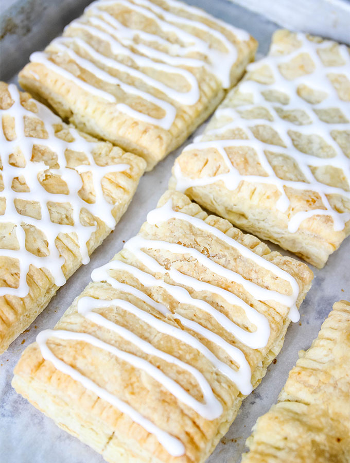 Homemade toaster strudels are cooled then topped with icing.