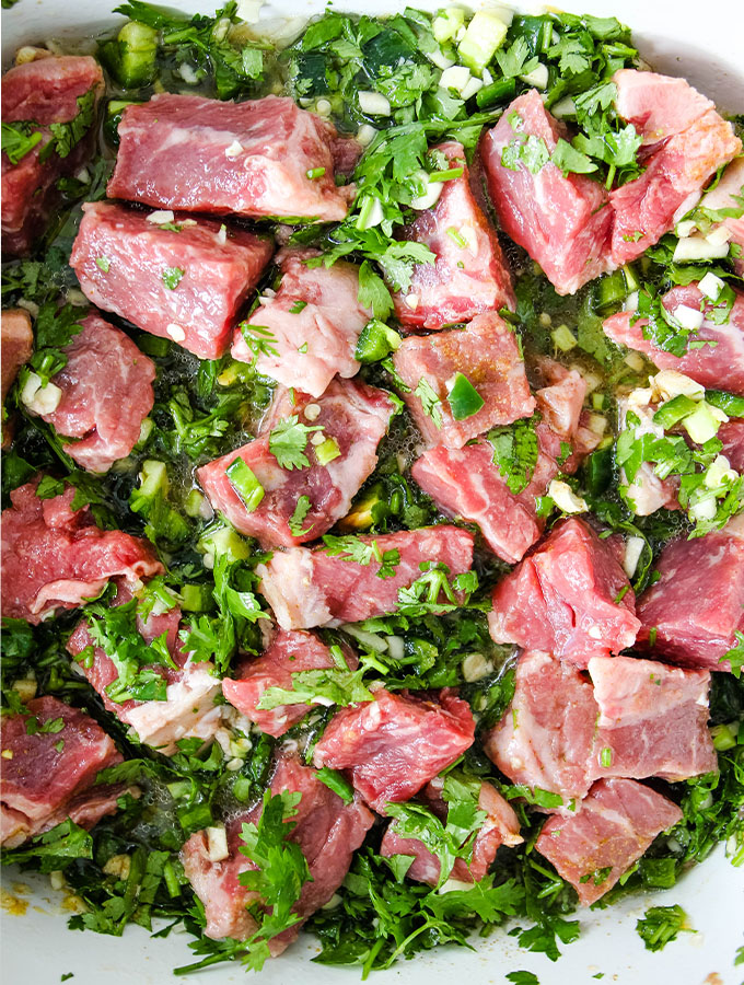 Carne asada ingredients are combined in a bowl and placed in the fridge to marinate for a few hours.