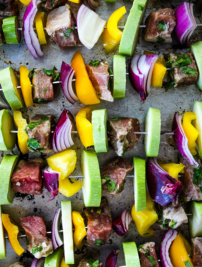 Grilled Carne Asada Kabobs is placed on a baking sheet in preparation of grilling.