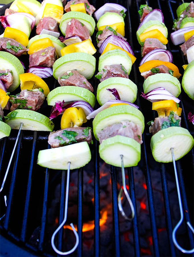 Grilled Carne Asada Kabobs are placed on a charcoal grill for cooking.